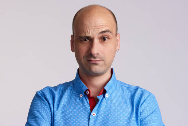 confused bald man raised eyebrow. confused bald man raised eyebrow. Isolated on grey raised eyebrows stock pictures, royalty-free photos & images