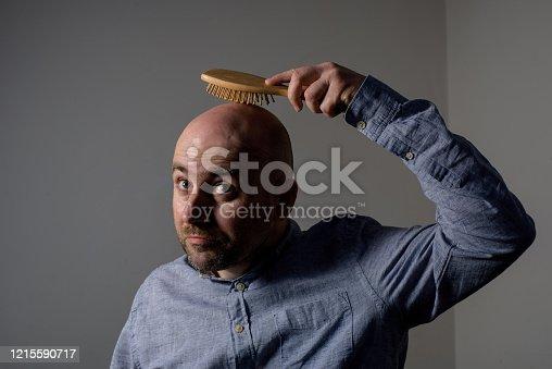 1162960006 istock photo Confused bald man with hair brush 1215590717
