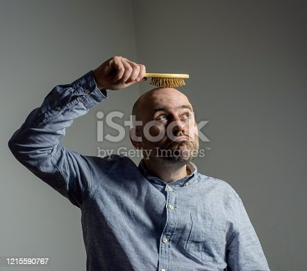 1162960006 istock photo Confused bald man with hair brush 1215590767