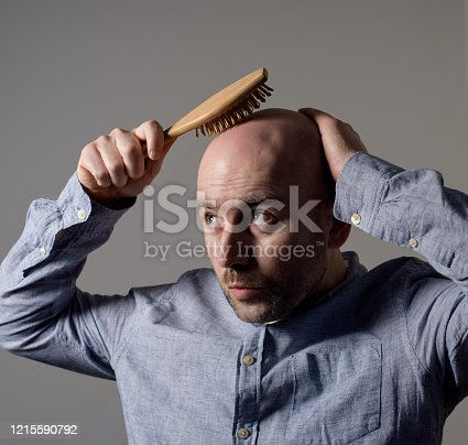 1162960006 istock photo Confused bald man with hair brush 1215590792