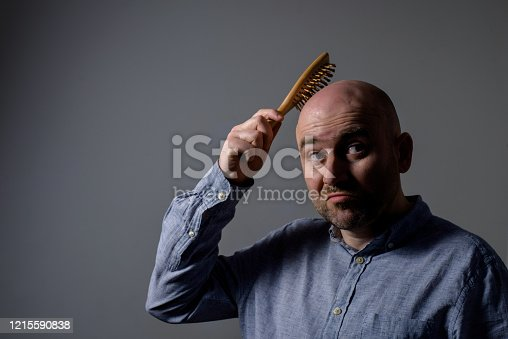 1162960006 istock photo Confused bald man with hair brush 1215590838