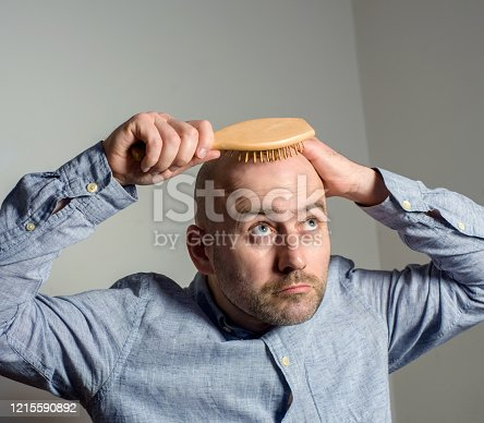 1162960006 istock photo Confused bald man with hair brush 1215590892