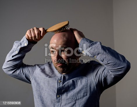 1162960006 istock photo Confused bald man with hair brush 1215590908