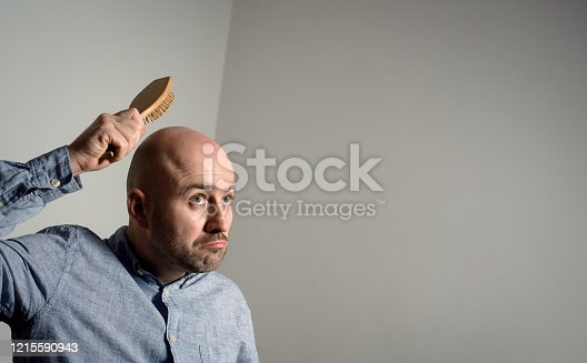 1162960006 istock photo Confused bald man with hair brush 1215590943
