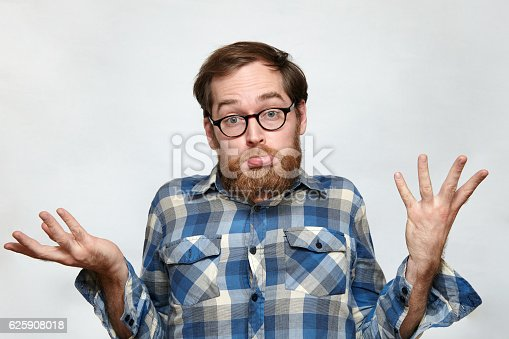 Man with beard and eyeglasses shrugging his shoulders in confusion, arms raised, isolated on gray