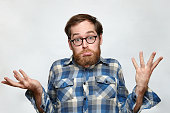 Confused bearded man in eyeglasses shrugging his shoulders