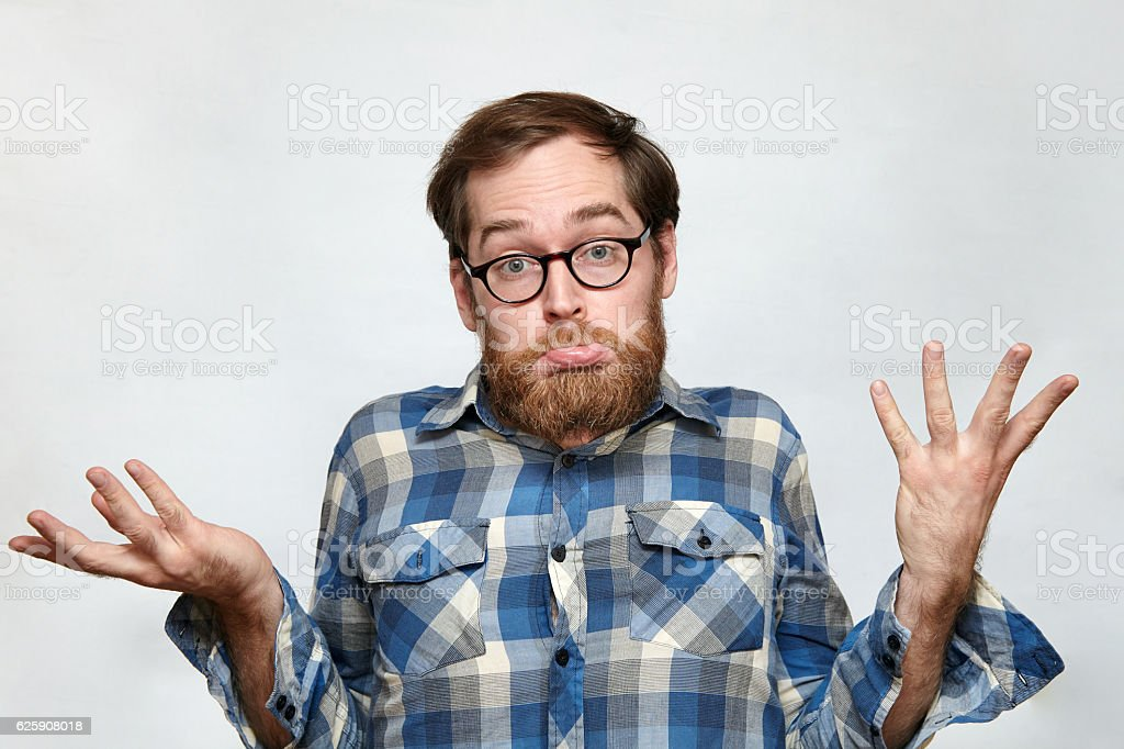 Confused bearded man in eyeglasses shrugging his shoulders stock photo