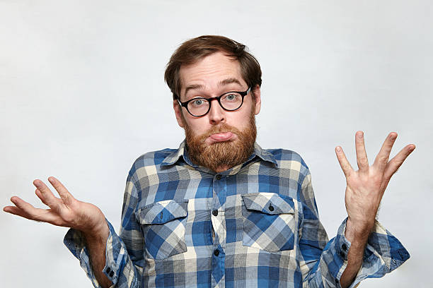 Confused bearded man in eyeglasses shrugging his shoulders Man with beard and eyeglasses shrugging his shoulders in confusion, arms raised, isolated on gray shrugging stock pictures, royalty-free photos & images