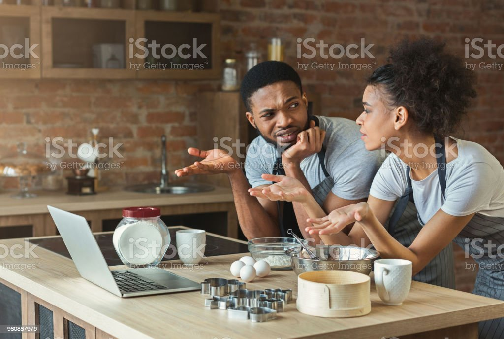 Confused black couple cooking pastry with recipe on laptop stock photo