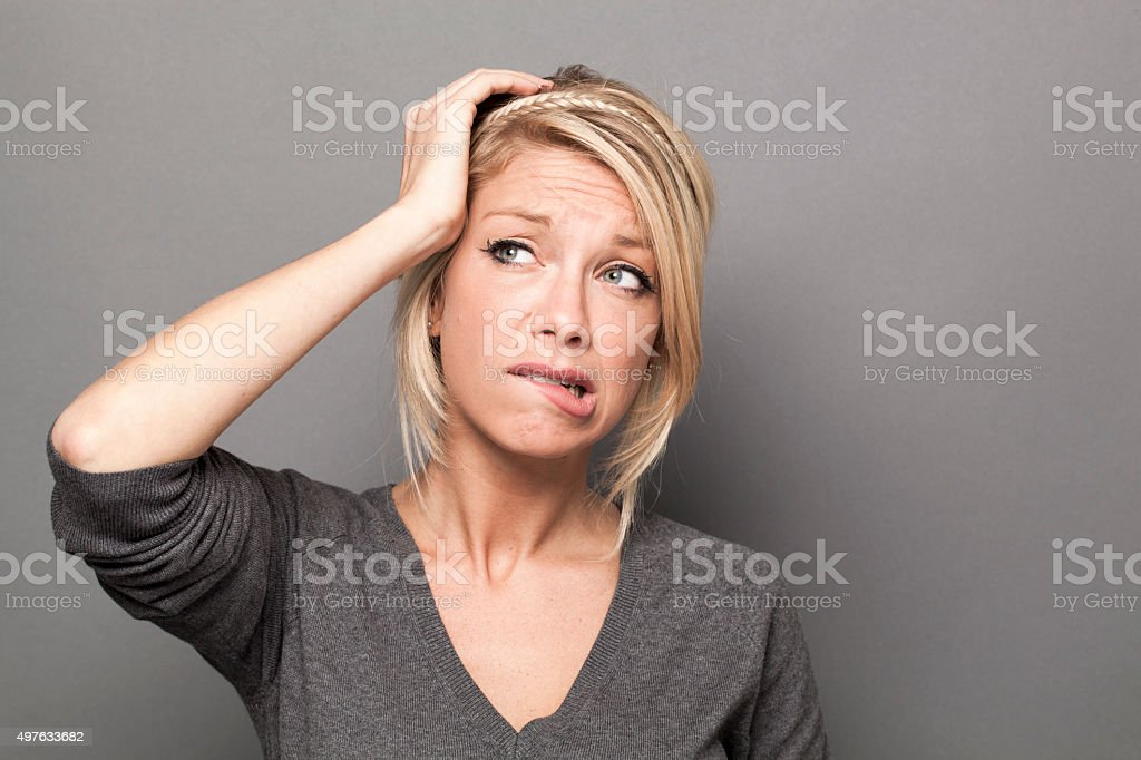confused blond girl expressing fear and suspicion with her face stock photo