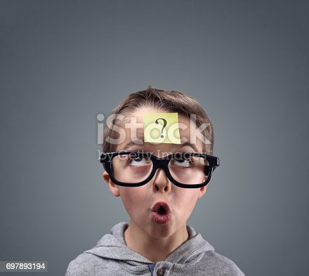 istock Confused boy thinking with question mark 697893194