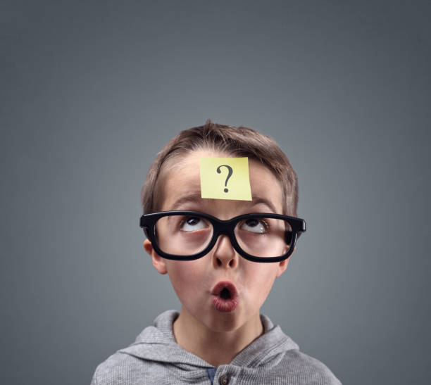 Confused boy thinking with question mark stock photo