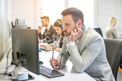 932342408istockphoto Confused business man with headset and eyeglasses in hand looking at desktop computer screen while working at his workplace in office 1136367662