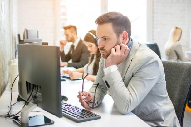 Verwirrter Geschäftsmann mit Headset und Brille in der Hand mit Blick auf Desktop-Computer-Bildschirm während der Arbeit an seinem Arbeitsplatz im Büro – Foto