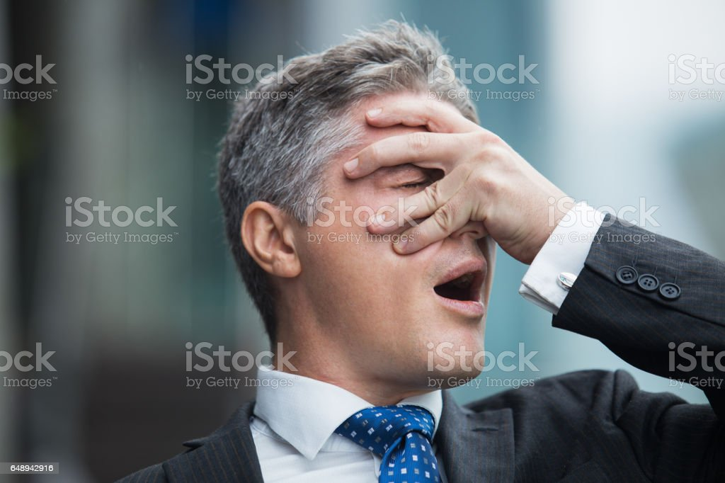 Confused businessman covering face with hand stock photo