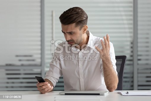 857213750istockphoto Confused businessman having problem with cellphone, receive bad news 1191319828