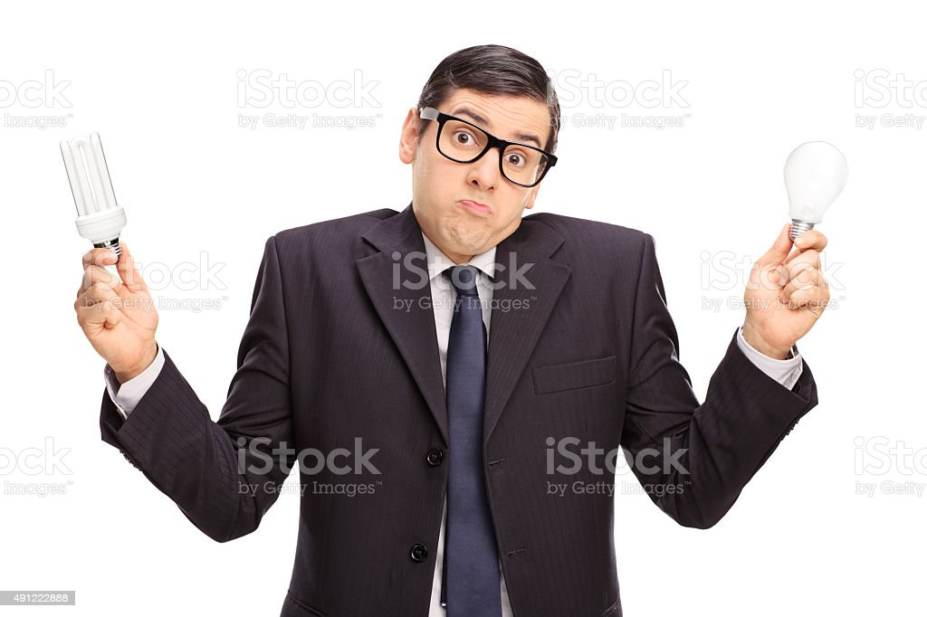 Confused businessman holding two light bulbs stock photo