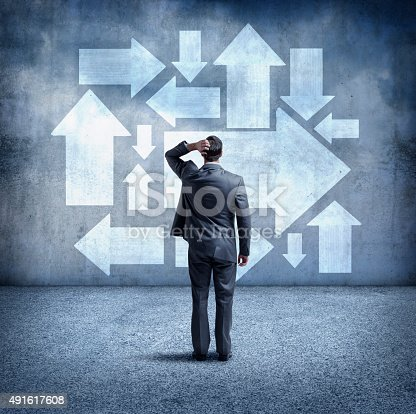 istock Confused Businessman Looking At Arrows Pointing In Different Directions 491617608