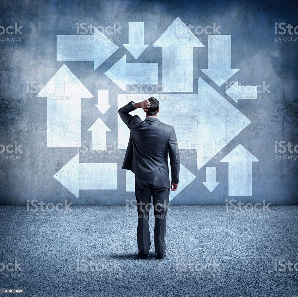 Confused Businessman Looking At Arrows Pointing In Different Directions stock photo