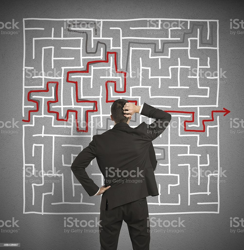 Confused businessman trying to solve labyrinth stock photo