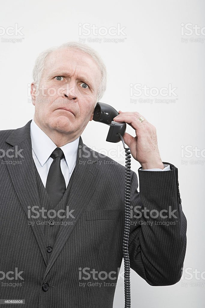 Confused businessman using a telephone stock photo