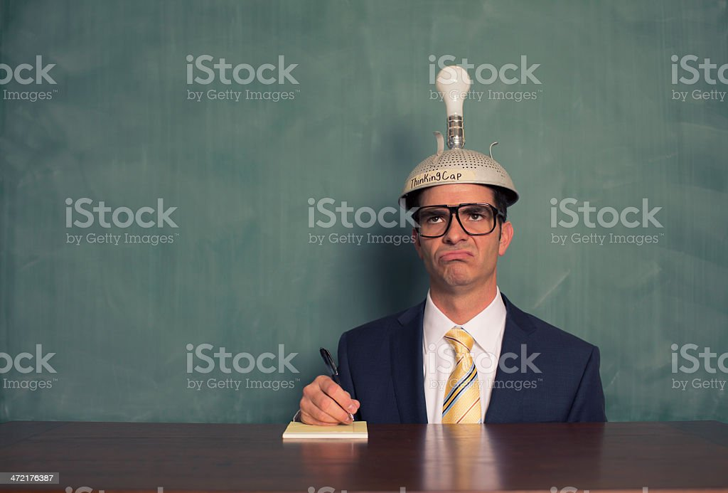 Confused Businessman Wearing Unlit Thinking Cap at Desk stock photo