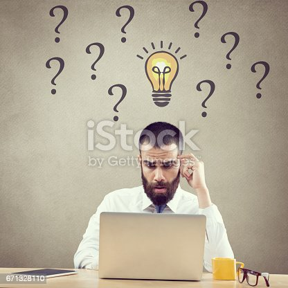 istock Confused businessman working on laptop 671328110