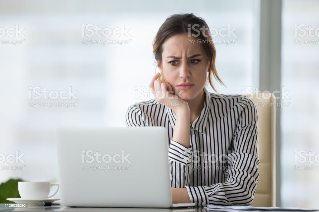 Confused businesswoman annoyed by online problem looking at laptop Confused businesswoman annoyed by online problem, spam email or fake internet news looking at laptop, female office worker feeling shocked about stuck computer, bewildered by scam message or virus Adult Stock Photo