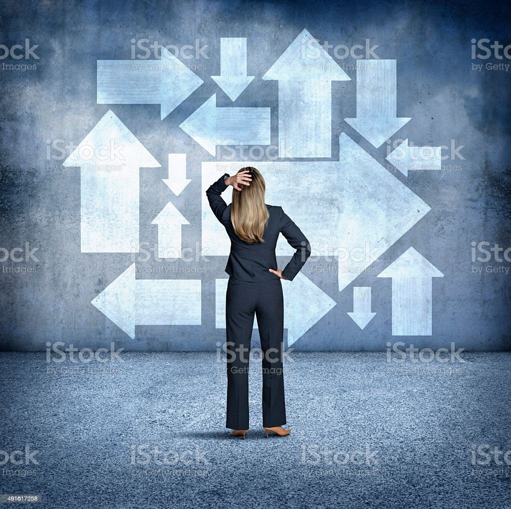 Confused Businesswoman Looking At Arrows Pointing In Different Directions stock photo