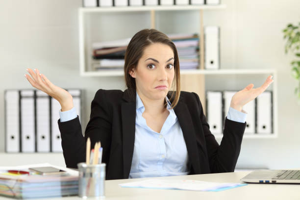 Confused businesswoman looking at camera Front view portrait of a confused businesswoman shrugging shoulders looking at camera at office ambiguity stock pictures, royalty-free photos & images