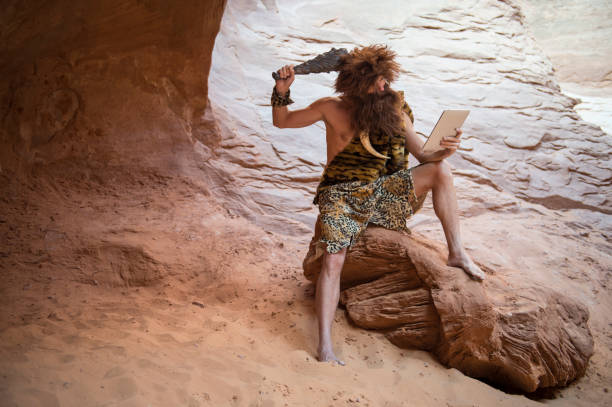 Confused Caveman Looking at Modern Tablet Stone Age luddite caveman scratching his head with a club while looking at his stone tablet outdoors in a weathered rock cave man cave stock pictures, royalty-free photos & images