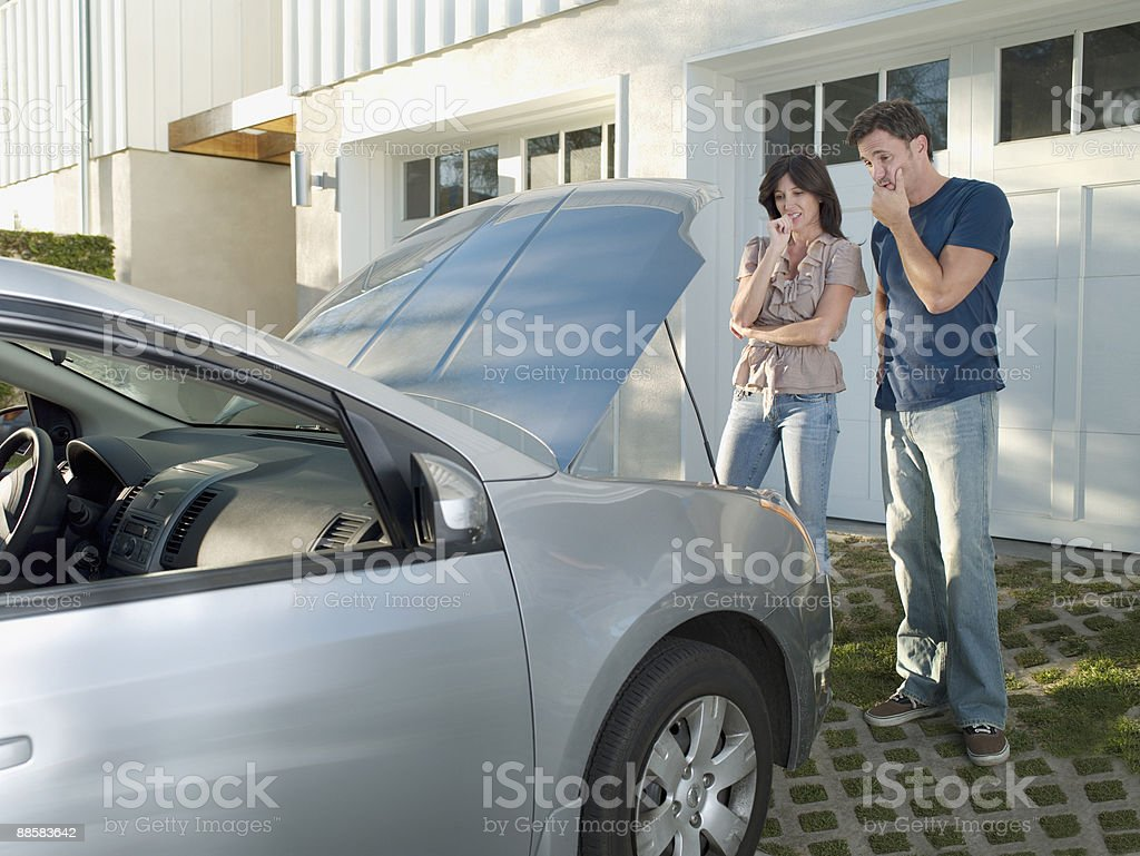 Confused couple looking at car engine royalty-free stock photo