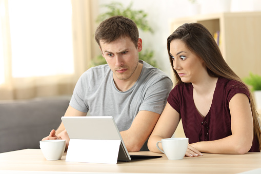 istock Confused couple receiving on line news 833135580