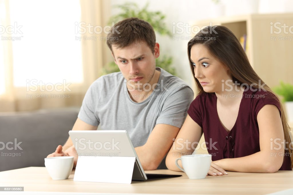 Confused couple receiving on line news stock photo