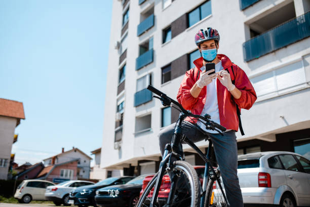 Confused delivery person trying to orientate while using GPS on his mobile phone so he could deliver on time stock photo