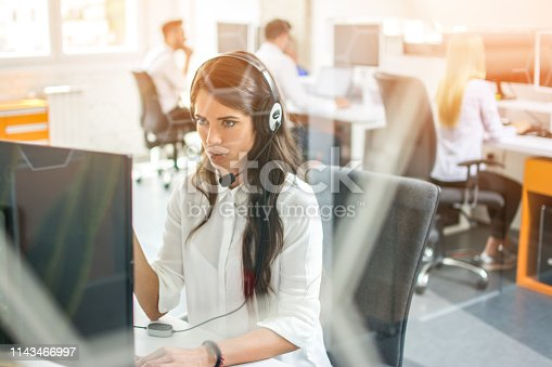istock Confused female customer support operator working on computer at her workplace in call center 1143466997