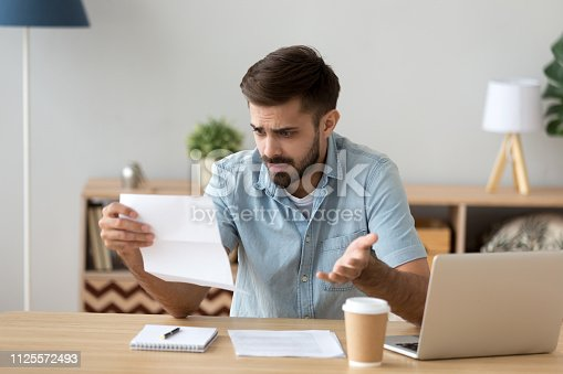istock Confused frustrated man holding mail letter reading shocking unexpected news 1125572493