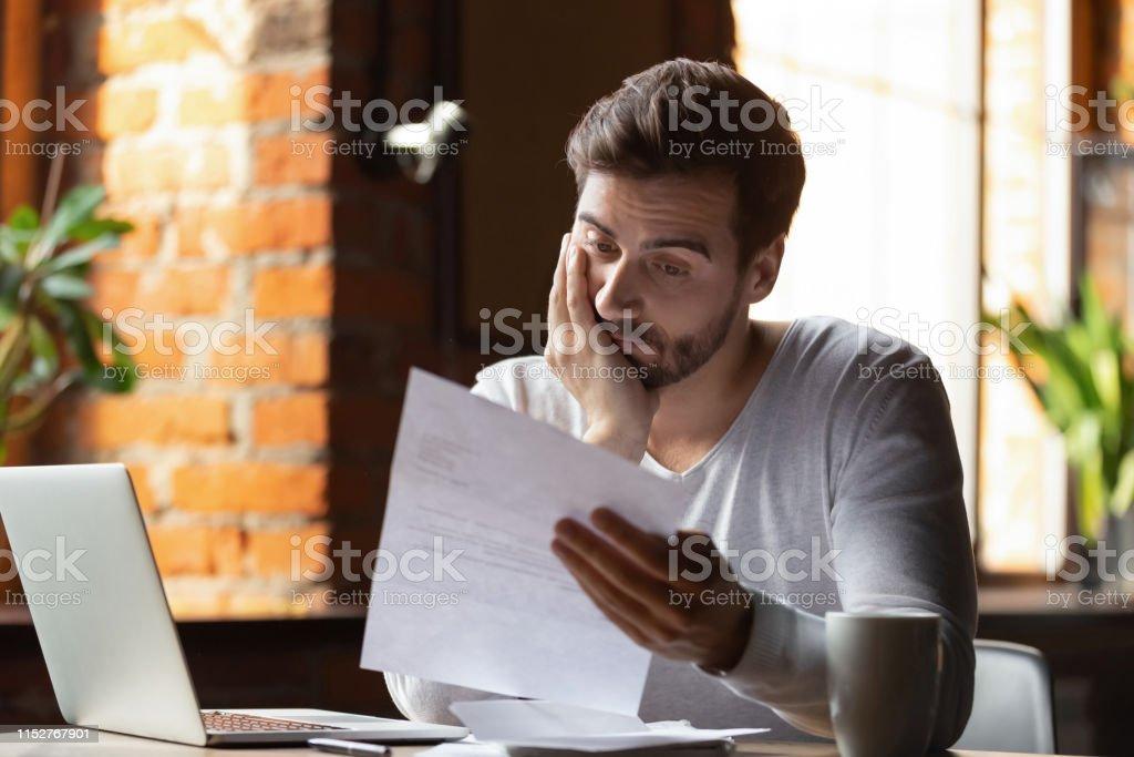 Confundido hombre frustrado leyendo carta en el café, recibiendo malas noticias - Foto de stock de Acontecimientos en las noticias libre de derechos