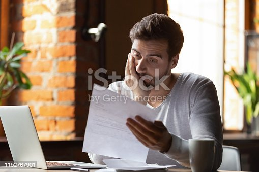 istock Confused frustrated man reading letter in cafe, receiving bad news 1152767901