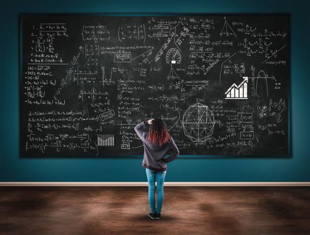 confused girl in front of a blackboard full of formulas. - formula 1 стоковые фото и изображения