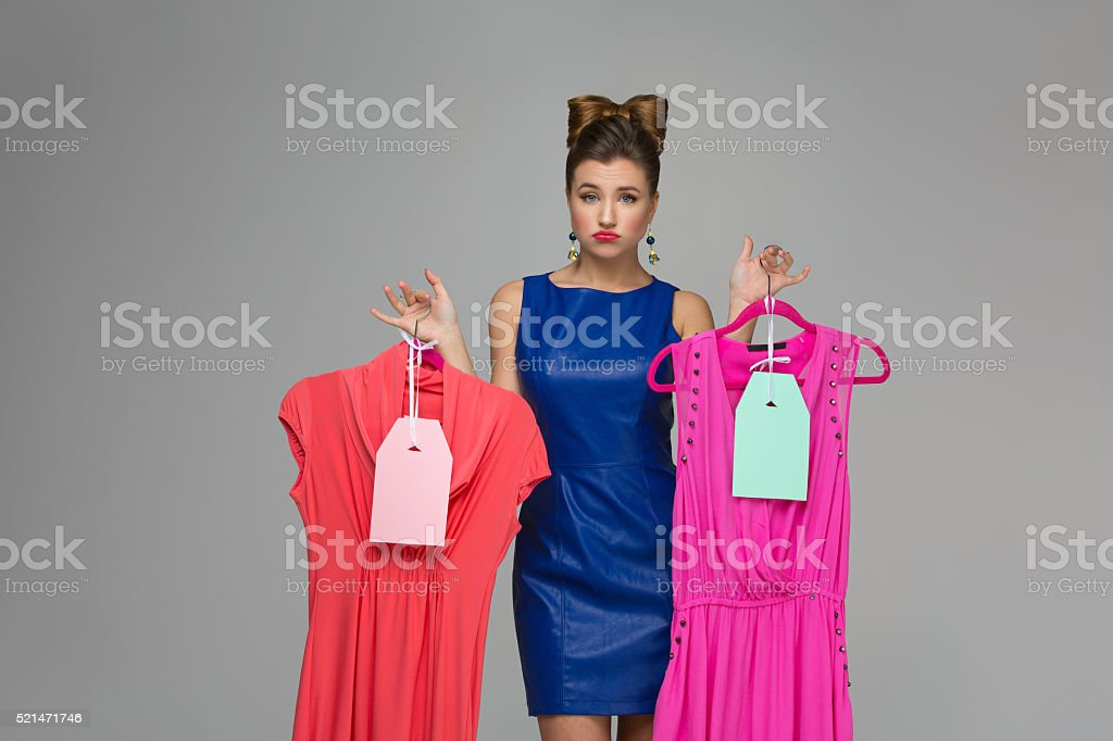 Confused girl with dresses stock photo