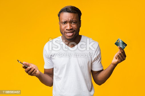 1173546354 istock photo Confused Guy Holding Smartphone And Credit Card Posing In Studio 1188580452