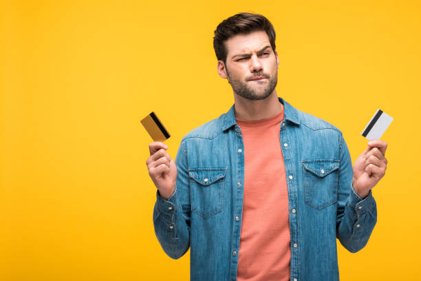 confundido hombre guapo sosteniendo tarjetas de crédito aisladas en amarillo - foto de stock