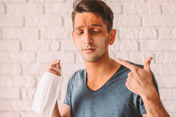 verwirrter hipster-mann zeigt auf sein gesicht mit lustigen sonnenbräunen - ffp2 stock-fotos und bilder