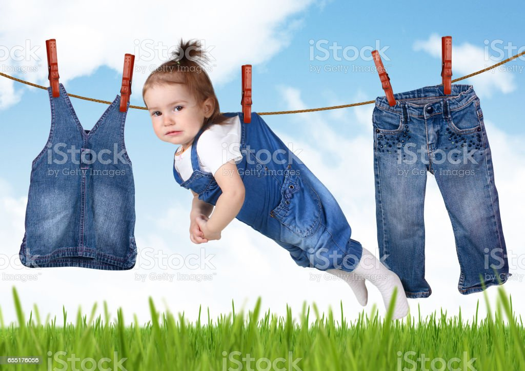 confused housework creative concept, Funny child hanging on clothesline stock photo