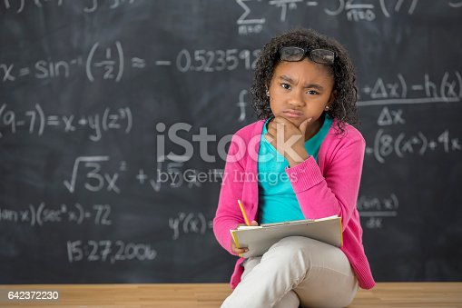 istock Confused little girl works on math homework 642372230