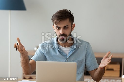 Shocked male worker look at laptop witnessing virus attack result in data loss, confused man using computer stare at screen seeing malfunction warning or notification, guy scared having pc breakdown