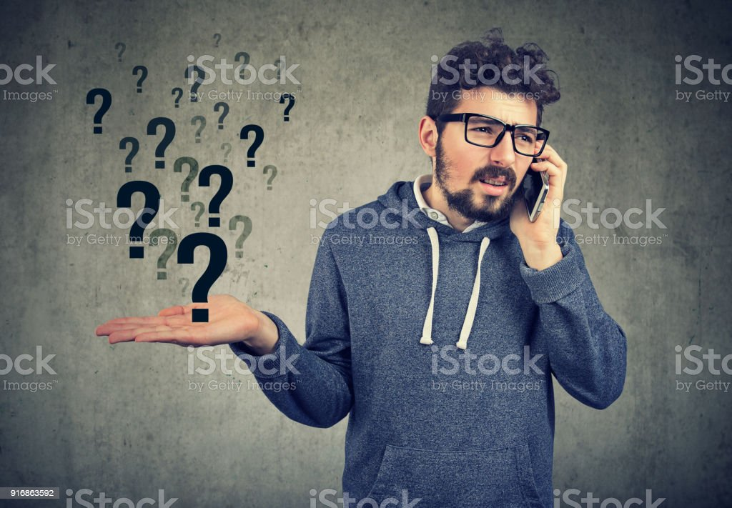 Confused man having phone call stock photo