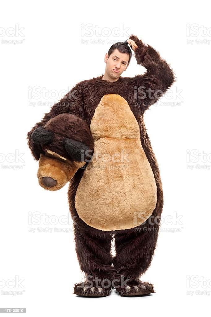 Confused man in bear costume scratching his head stock photo