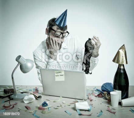 618210072 istock photo Confused man in office interior after New Year's Day party 165918470